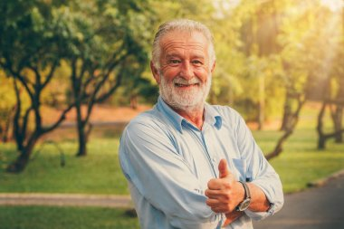 Portrait of happy senior man standing in the park. Elder health and retirement concept.