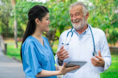 Senior doctor with young doctor in the park. Medical healthcare staff and doctor service.