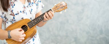 Happy woman musician playing ukulele and singing a song in sound studio. Music lifestyle concept.