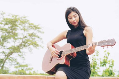 Happy woman plays guitar with nature background. Music and relaxation concept.