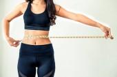 Detailní záběr záběr ženy s štíhlé tělo měření její pas a trup. Zdravá výživa a hubnout losing koncept.