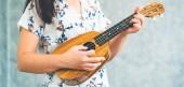 Musicista di donna felice suonare ukulele e cantando una canzone in studio di registrazione. Concetto di lifestyle musica.
