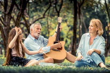 Happy family play guitar and sing together while sitting in the park in summer. Concept of family bonding by music.