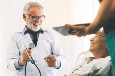 Mature doctor talking and examining health of senior patient in hospital ward. Medical healthcare and doctor staff service concept.