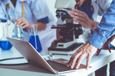Group of scientists wearing lab coat working in laboratory while examining biochemistry sample in test tube and scientific instruments. Science technology research and development study concept.