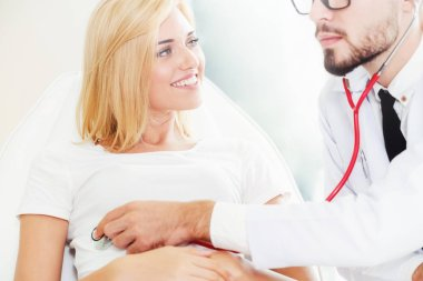 Male doctor is talking and examining female patient in hospital office. Healthcare and medical service.