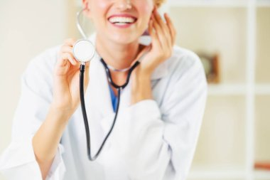 Young female doctor pointing stethoscope at blank space. Selective focus at doctors hand. Medical healthcare concept.