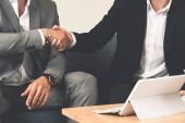 Podnikatel handshake s jiným partnerem podnikatel v moderní pracoviště úřadu. Lidé firemní obchodní nabídky koncept.