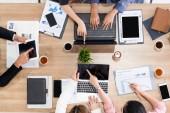 Fényképek Felülnézet üzletember vezetői a csoport értekezletet más üzletemberek és üzletasszonyok, laptop számítógép, a kávé és a dokumentum modern hivatalban asztalra. Emberek vállalat üzleti csapat koncepció.