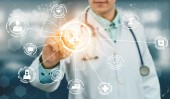 Fotografie Medical Healthcare Concept - Doctor in hospital with digital medical icons graphic banner showing symbol of medicine, medical care people, emergency service network, doctor data of patient health.