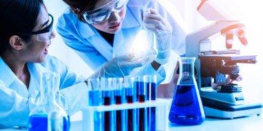 Laboratuvarda deney tüpü ve bilimsel aletlerdeki biyokimya örneklerini incelerken laboratuvar önlüğü giyen bir grup bilim adamı. Bilim teknolojisi araştırma ve geliştirme konsepti.