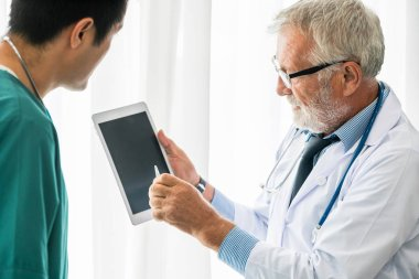 Doctors working with tablet computer at hospital.