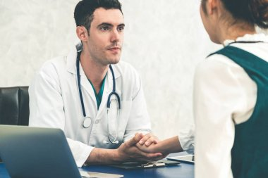 Young doctor examining patient in hospital office.