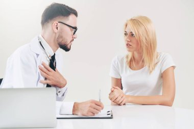 Male Doctor and Female Patient in Hospital Office
