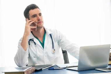 Doctor working in hospital office.