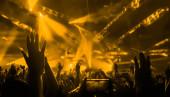 Happy people dance in nightclub DJ party concert and listen to electronic dancing music from DJ on the stage. Silueta veselý dav oslavit Silvestr party2020. Lidé životní styl DJ noční život.