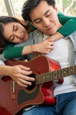 Young Asian Couple Plays Guitar and Sing Song in Living Room at Home Together. Music and Lifestyle concept.