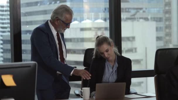 Senior manager dává rady mladé ženě pracovnice.
