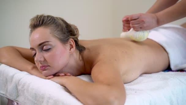Massagetherapeutin mit Kräuterkompresse auf Frau.