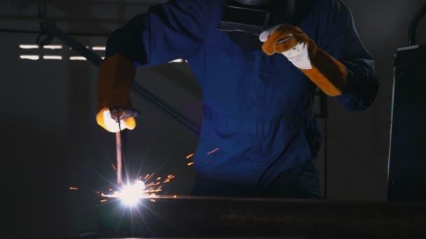 Kovový svářeč pracující s obloukovým svařovacím strojem