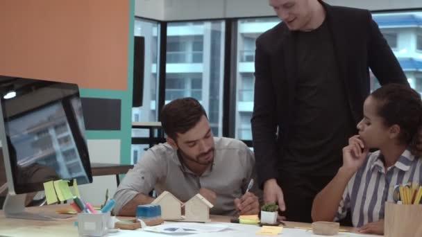 Kreative Geschäftsleute unterhalten sich am Schreibtisch am Arbeitsplatz.
