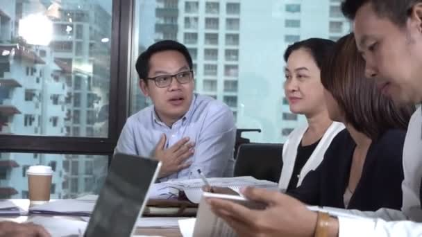 Asian business people discuss marketing strategy.