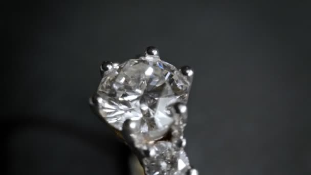 Extreme Detailaufnahmen von Diamantringen in Nahaufnahme, während sie auf dunklem Hintergrund rotieren