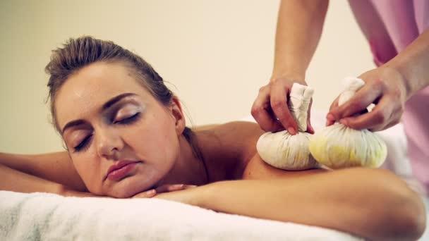 Masszázs terapeuta használ gyógynövény borogatás, hogy nem a kezelés a nő fekszik a spa ágy egy luxus spa üdülőhely. Wellness, stresszoldó és fiatalító koncepció.