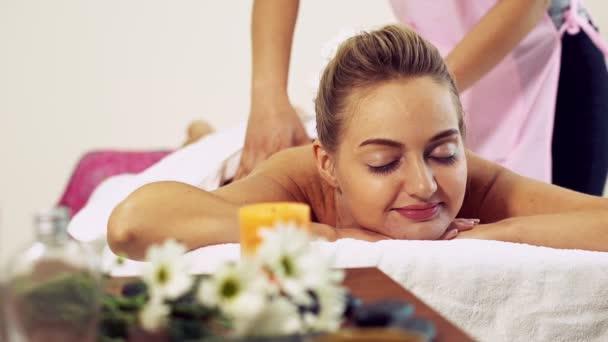 Relaxovaná žena dostává masáž zad v luxusních lázních s profesionálním masážním terapeutem. Wellness, léčebný a relaxační koncept.