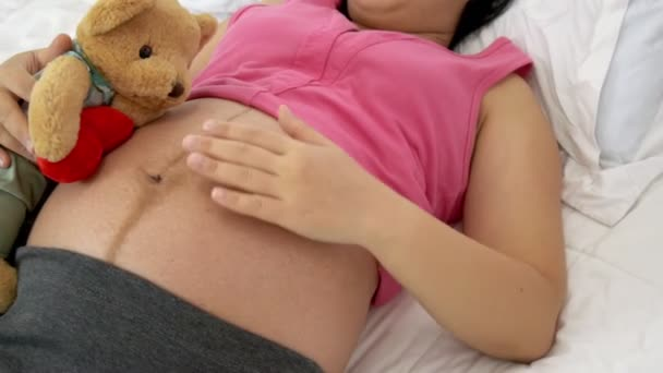 Happy pregnant woman sleeping on bed in bedroom at home for resting and stress relief. The young expecting mother holding baby in pregnant belly. Maternity prenatal care and woman pregnancy concept.
