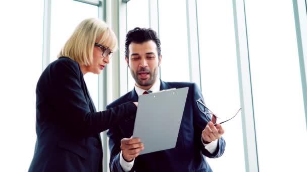Dva obchodníci mluví o strategii projektu v kanceláři zasedací místnosti. Podnikatel diskutovat plánování projektu s kolegou na moderním pracovišti při konverzaci a poradenství v oblasti finančních dat sestavy.
