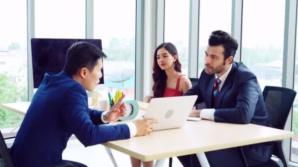 Chytrý podnikatel a obchodnice mluví na skupinové schůzce u kancelářského stolu v moderním kancelářském interiéru. Strategické plánování obchodní spolupráce a brainstorming spolupracovníků.
