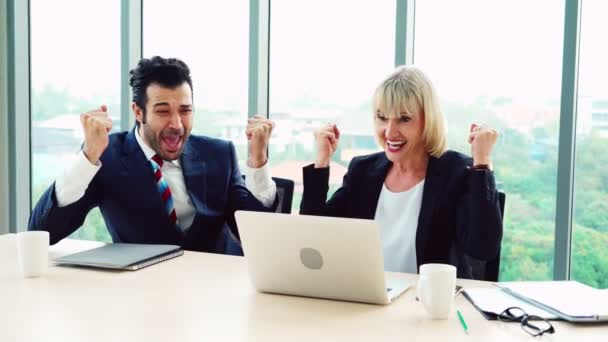 Two happy business people celebrate at office