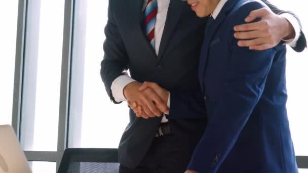 Podnikatelé podání ruky v kanceláři společnosti