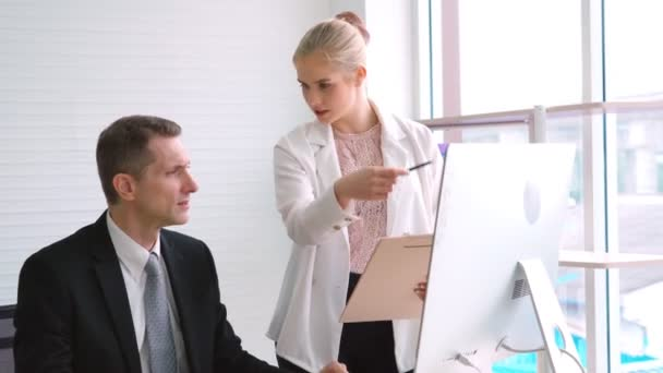 Two business people talk project strategy at office