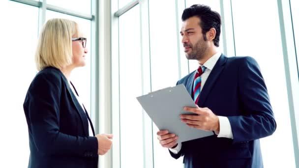 Két üzletember megbeszéli a projektstratégiát az irodában.