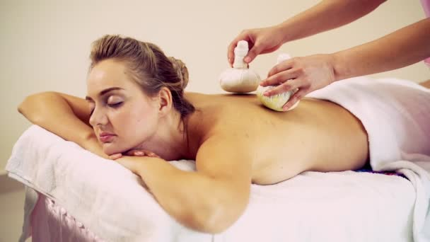 Masážní terapeut pomocí bylinné obklady na ženy.