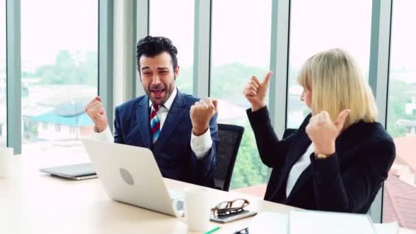 Zwei glückliche Geschäftsleute feiern im Büro