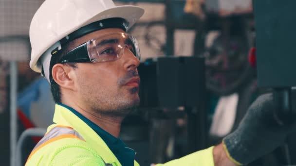 Kluger Fabrikarbeiter mit Maschine in Fabrikhalle
