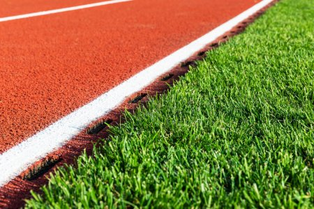 Photo for Creative abstract competition concept: macro view of the fragment of red running track and green grass field at the sport stadium with selective focus effect - Royalty Free Image
