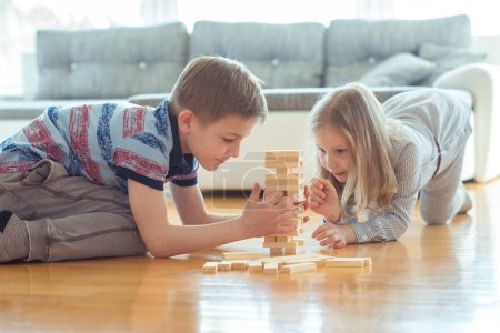 Photo for Two happy siblings playing a game with wooden blocks at home joyfully - Royalty Free Image