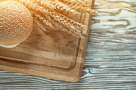 Carving board bread wheat ears on wooden surface