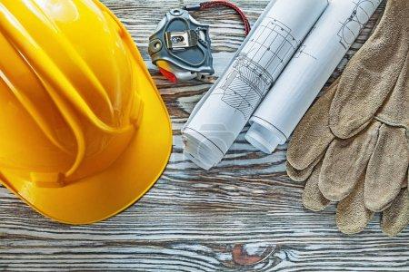 Photo pour Ruban à mesurer gants de sécurité dessins de construction chapeau dur sur une planche de bois vintage . - image libre de droit