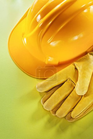 Protective gloves building helmet on yellow background.