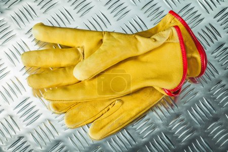 Photo for Leather protective gloves on corrugated metal texture. - Royalty Free Image