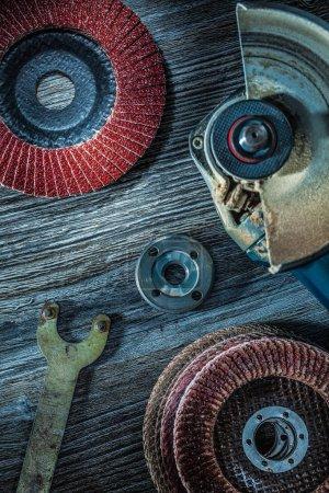 Angle grinder sanding discs key on vintage wooden board.
