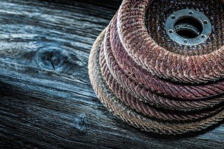 Pile of radial sanding discs on vintage wooden board.