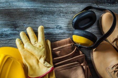 Photo pour Gants de protection en cuir bottes ceinture d'outils casque casque protecteur sur planche en bois . - image libre de droit