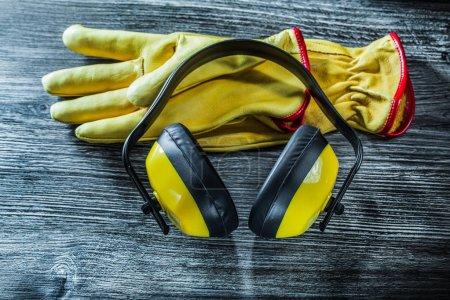 Photo pour Gants de sécurité cache-oreilles sur planche de bois. - image libre de droit
