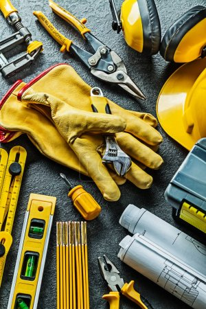 Photo pour Version verticale grand ensemble d'outils de construction avec gants au centre sur fond noir - image libre de droit